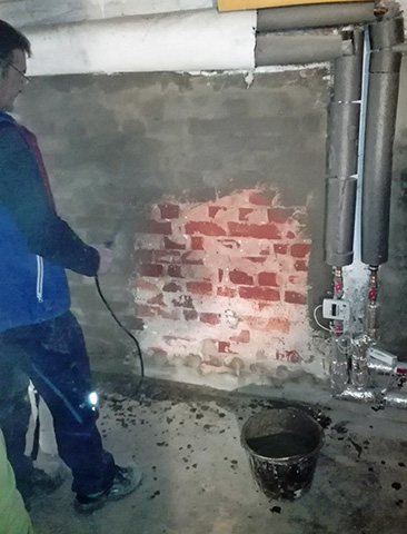 Drying out the basement from the inside: moisten the wall, apply sealing slurry